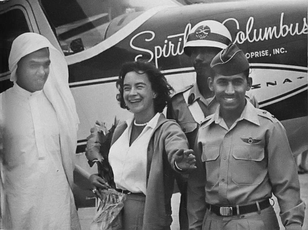 Jerrie Mock in Saudi Arabia with officers of the military and her airplane in background